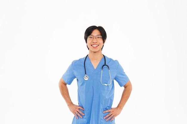 Médecin homme asiatique confiant en uniforme et stéthoscope debout isolé sur mur blanc