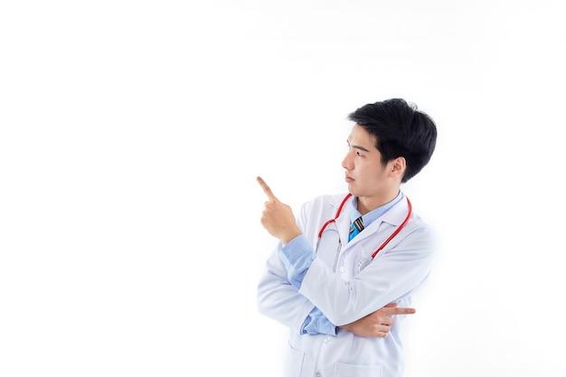 Médecin de l'homme asiatique dans une robe médicale stéthoscope pointant l'index de côté sur l'espace de copie isolé sur mur blanc