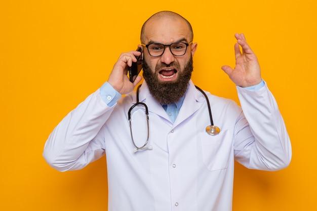 Médecin homme barbu en blouse blanche avec stéthoscope autour du cou portant des lunettes criant avec une expression agressive tout en parlant au téléphone mobile
