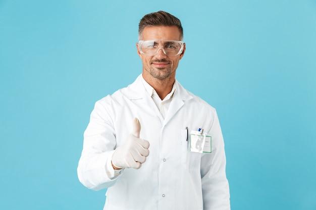 Médecin homme confiant en uniforme debout isolé sur mur bleu, donnant les pouces vers le haut
