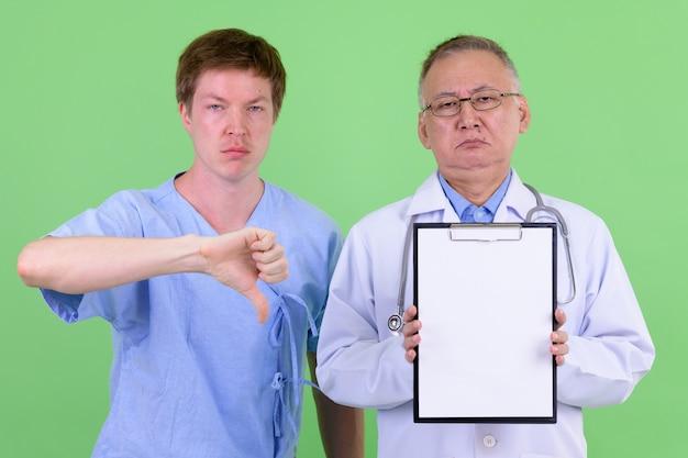 Médecin de l'homme japonais mature et patient scandinave ensemble contre la clé de chrominance avec mur vert