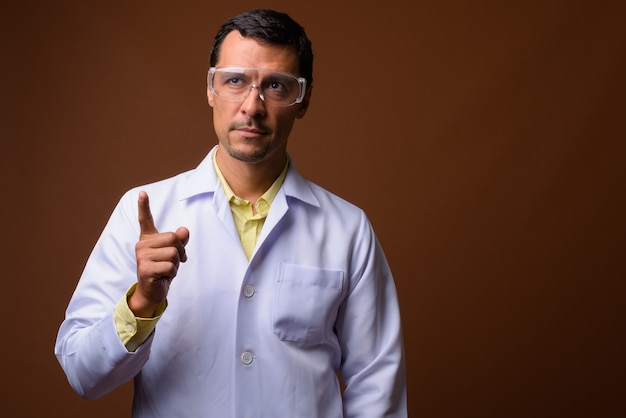 Médecin de l'homme portant des lunettes de protection tout en pointant le doigt vers le haut et en pensant