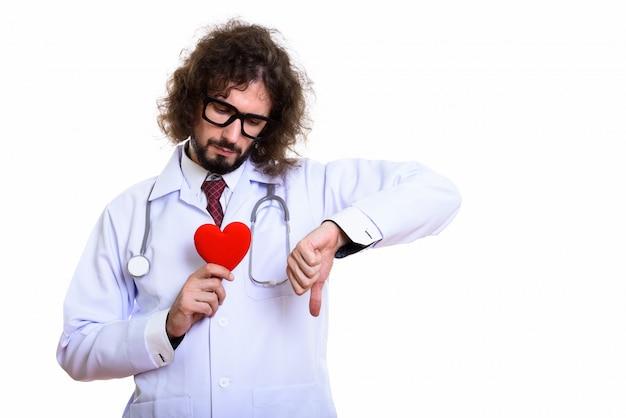 Médecin homme triste tenant un coeur rouge tout en donnant le pouce vers le bas