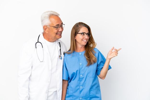Médecin et infirmière d'âge moyen isolés sur fond blanc présentant une idée tout en regardant en souriant vers