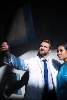 Médecin et infirmière examinant le rapport de radiographie