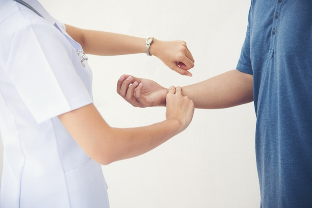 Médecin ou infirmière de la main examine l'homme patient de pouls de contrôle isolé.