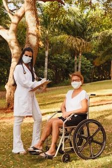 Médecin infirmière de prendre des notes sur le presse-papiers consultation femme âgée dans le jardin d'accueil