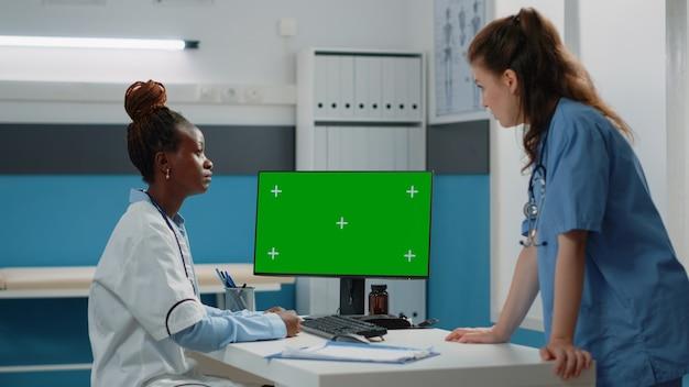 Médecin et infirmière travaillant avec un écran vert horizontal