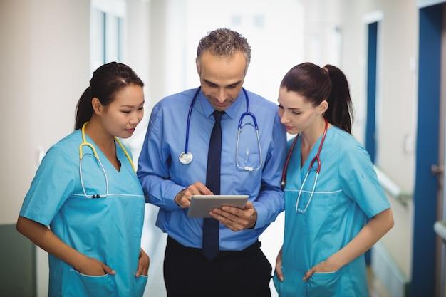 Médecin et infirmières discutant sur tablette numérique