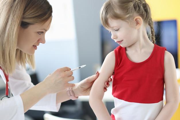 Un médecin inocule une petite fille à l'épaule