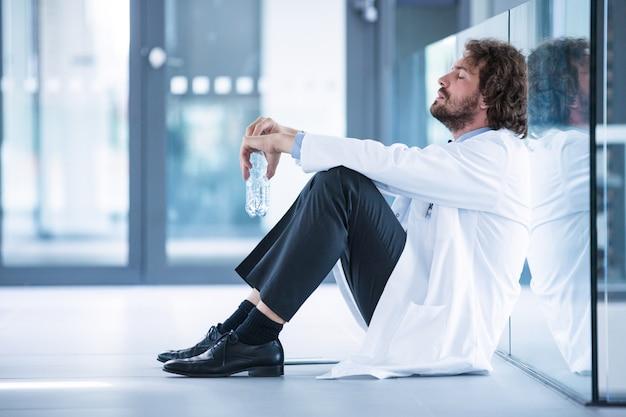 Médecin inquiet, assis sur le sol