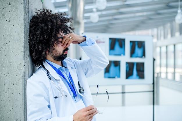 Médecin inquiet et fatigué debout à l'hôpital, concept de virus corona. espace de copie.