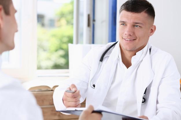 Médecin inquiet offrant un stylo