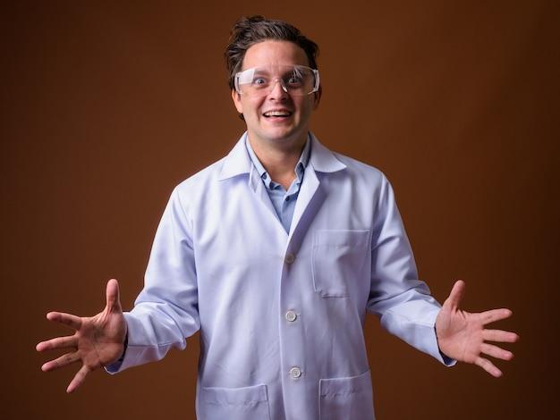 Médecin italien portant des lunettes de protection contre le mur marron