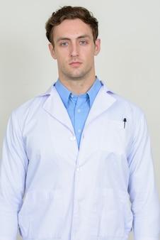 Médecin de jeune bel homme aux cheveux ondulés isolé