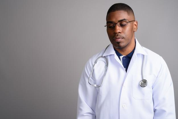Médecin de jeune homme africain beau sur fond gris