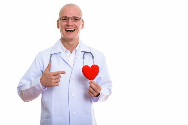 Médecin de jeune homme chauve heureux souriant tout en tenant et en pointant un coeur