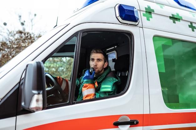 Médecin de jeune homme professionnel et confiant avec ambulance