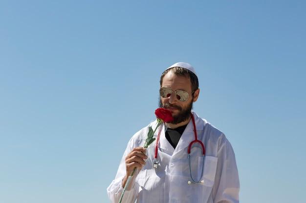 Médecin juif barbu en yarmulke blanc (chapeau, kippa, chapeau juif) portant des lunettes de soleil, un manteau et un stéthoscope reniflant une fleur de rose rouge. portrait bel homme américain posant et renifler du bouquet