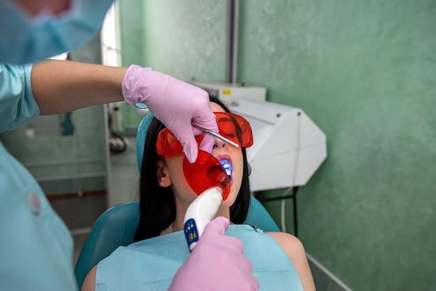 Médecin avec lampe et miroir traitant les dents des patients en gros plan