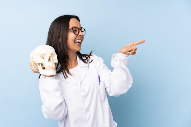 Médecin légiste de police femme sur mur isolé pointant le doigt sur le côté et présentant un produit