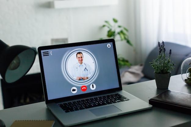 Médecin en ligne sur ordinateur portable à la maison