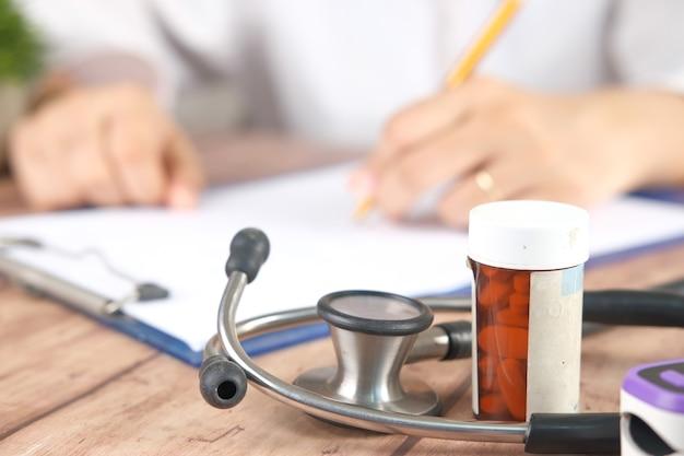 Médecin main écrit la prescription sur le bureau se bouchent