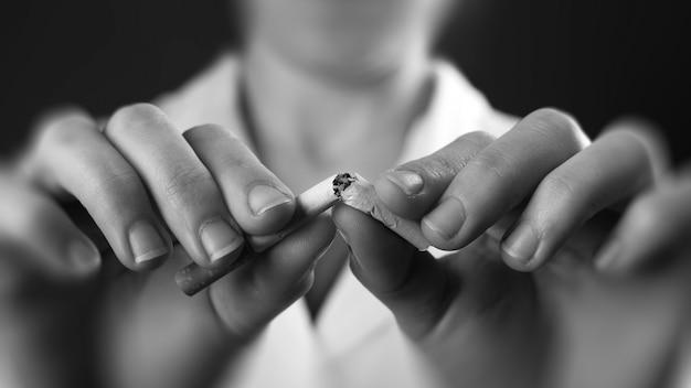 Médecin des mains casser un gros plan de cigarette. concept de nocivité du tabagisme.