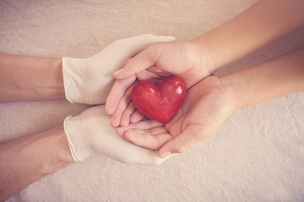 Médecin mains avec des gants tenant les mains de l'enfant, coeur rouge, assurance maladie, concept de don