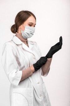 Médecin masqué en blouse blanche met des gants sur ses mains