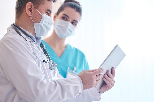 Médecin en masque et blouse de laboratoire à l'aide de tablette numérique tout en discutant de l'épidémie de grippe avec un collègue en clinique