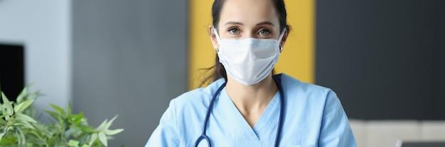 Médecin avec masque médical de protection de l'emplacement à table au bureau et écrit dans les documents