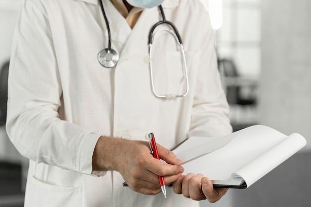 Médecin avec masque médical vérifiant ses notes