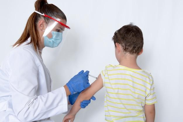 Médecin avec masque protecteur, l'inoculation du vaccin à un garçon de cinq ans