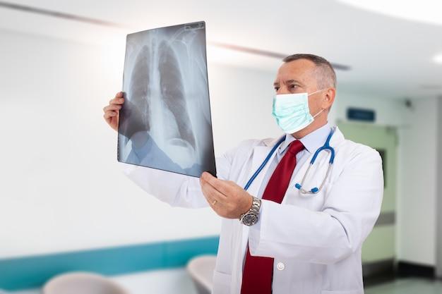 Médecin masqué tenant un concept de radiographie pulmonaire, de coronavirus et de pneumonie