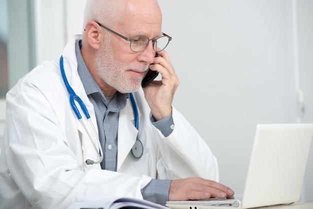 Médecin mature au téléphone à son bureau