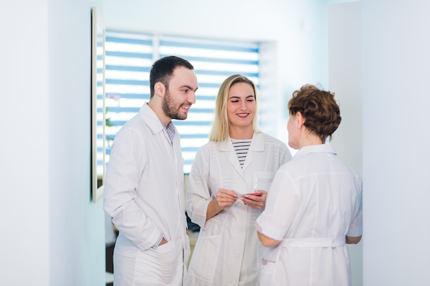 Médecin mature discutant avec des infirmières dans un hôpital de couloir. médecin discutant de l'état du cas du patient avec son personnel médical après l'opération.