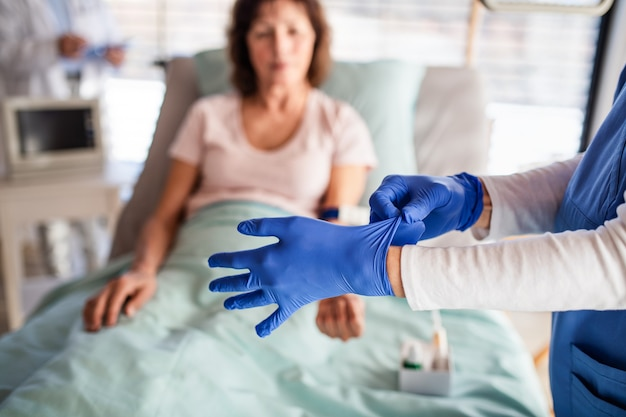 Un médecin méconnaissable avec un patient au lit à l'hôpital, mettant des gants.