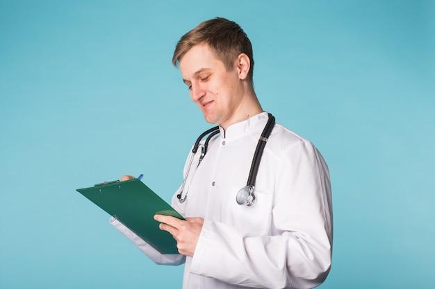 Médecin médecin homme sur fond bleu clinique.