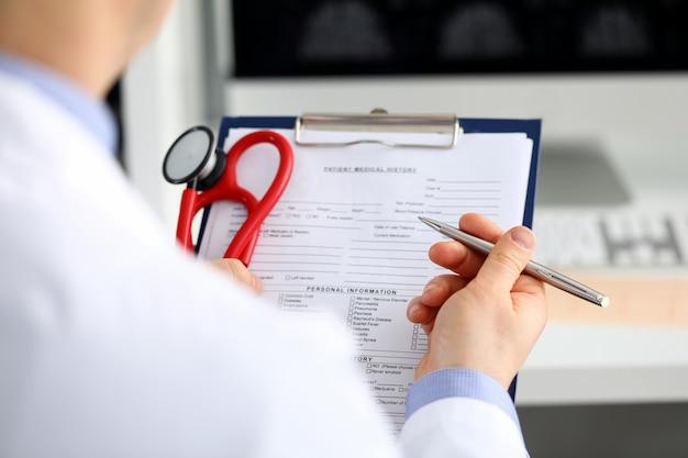 Médecin de médecine masculine main tenant un stylo argent écrit quelque chose sur le presse-papiers agrandi. tour de salle, visite de visite du patient, calcul médical et concept de statistiques. médecin prêt à examiner le patient