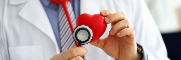 Médecin de médecine masculine tenant coeur rouge
