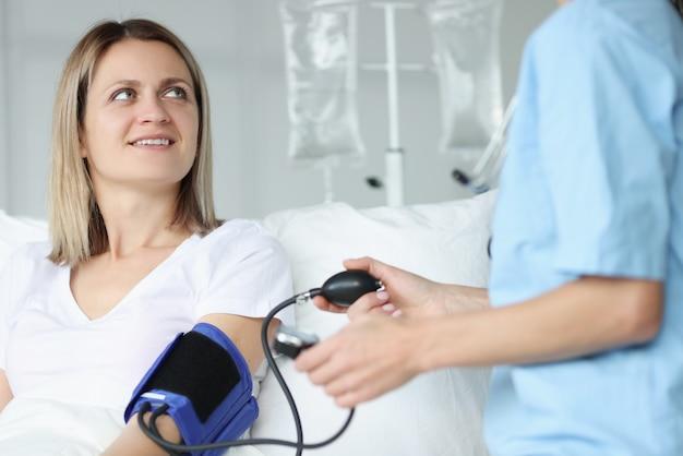 Médecin mesurant la pression artérielle avec tonomètre en clinique. hypertension artérielle chez les femmes enceintes concept