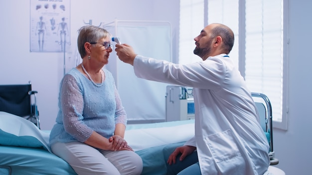 Médecin mesurant la température d'une femme âgée assise sur un lit d'hôpital. utilisation d'un thermomètre infrarouge numérique sans contact dans une clinique privée moderne. examen médical pour les infections et les maladies