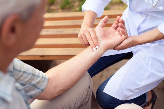 Le médecin mesure le pouls du patient assis sur un banc