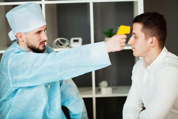 Un médecin mesure la température d'un patient lors d'une épidémie covid-19
