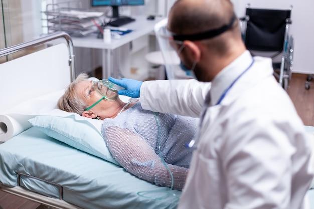 Médecin mettant un masque à oxygène sur une femme âgée allongée à l'hôpital pendant la pandémie de coronavirus