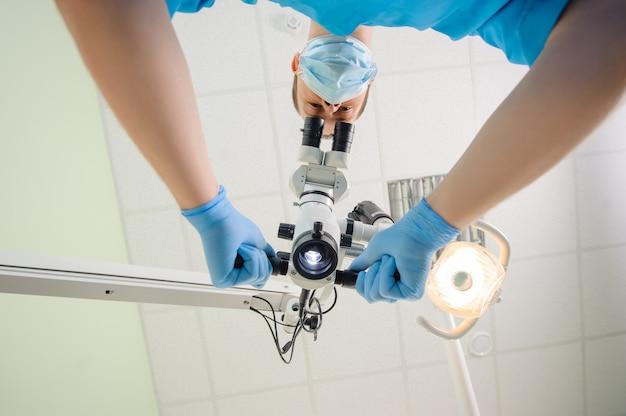 Médecin avec un microscope dans une clinique dentaire
