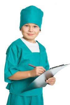 Médecin mignon garçon avec presse-papiers médical