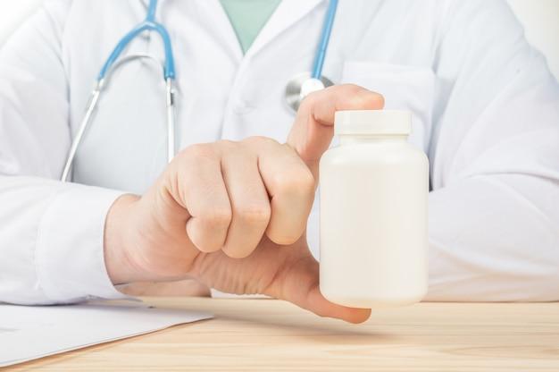 Médecin montrant une bouteille de pilules au patient. spécialiste détenant un grand pot de suppléments, nutrition riche en vitamines