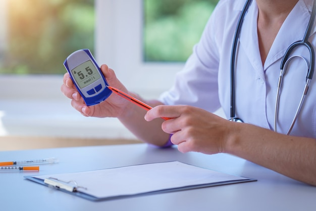 Un médecin montre un lecteur de glycémie avec une glycémie à un patient diabétique lors d'une consultation médicale et d'un examen à l'hôpital. mode de vie diabétique et soins de santé